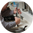 plumber repairing kitchen appliance